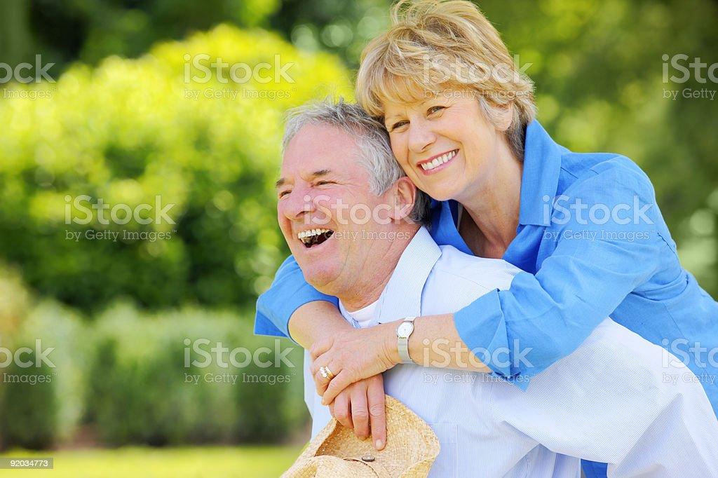 Happy active senior man giving piggyback ride to woman outdoors royalty-free stock photo