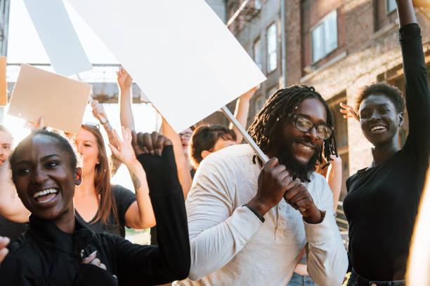 glücklich aktivisten durch die stadt marschieren - aktivist stock-fotos und bilder