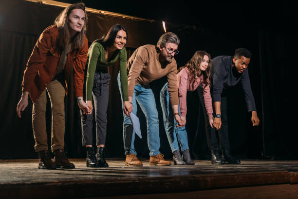 happy actors and actresses bowing on stage stock photo
