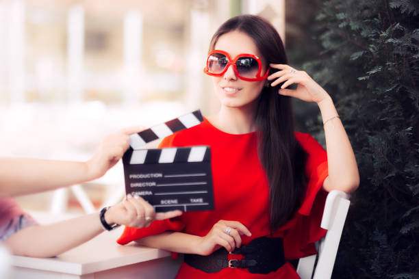 Happy Actress with Oversized Sunglasses Shooting Movie Scene Diva in red dress and big shades starring in an artistic film diva human role stock pictures, royalty-free photos & images