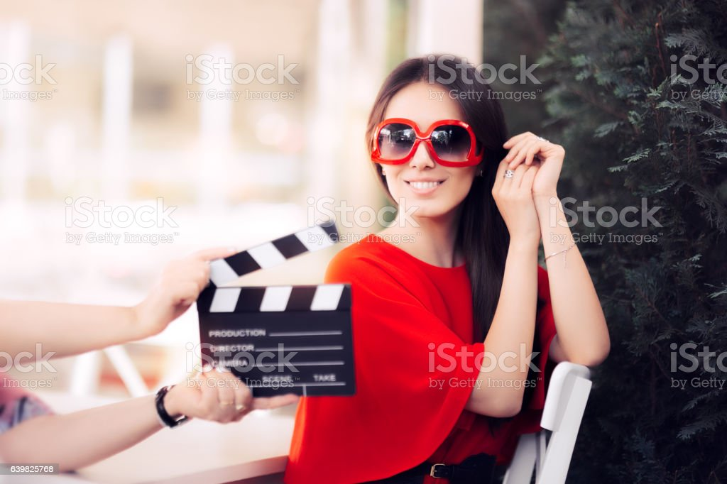 Happy Actress with Oversized Sunglasses Shooting Movie Scene stock photo