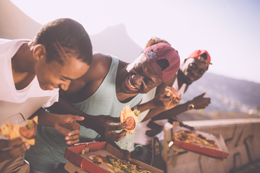 Group of adolescent friends laughing while happily sharing pizza