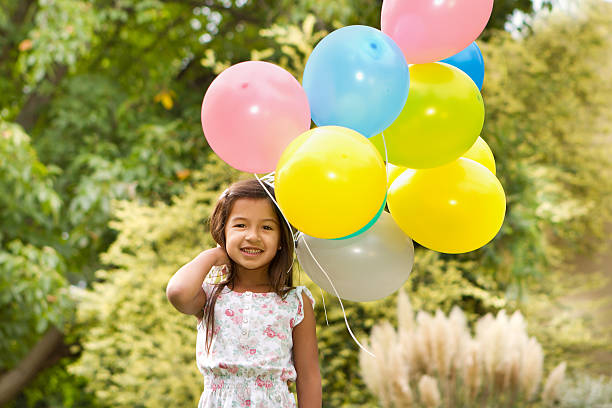 Happy adorable girl with balloons stock photo