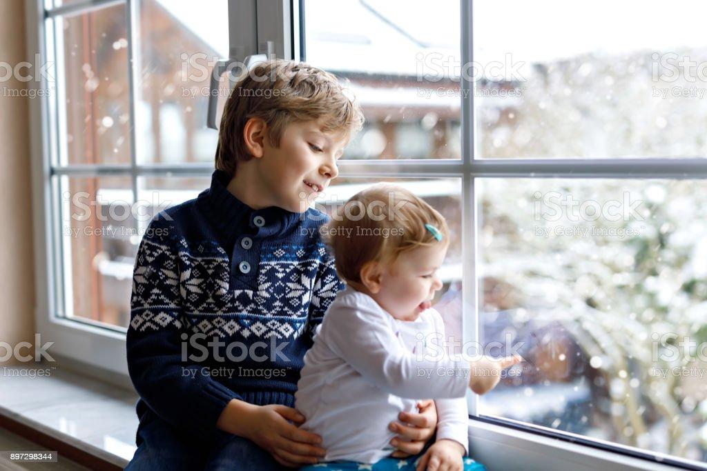 Feliz criança adorável menino e uma menina de bebê fofo sentado perto da janela e olhando do lado de fora neve no dia de Natal ou a manhã - foto de acervo