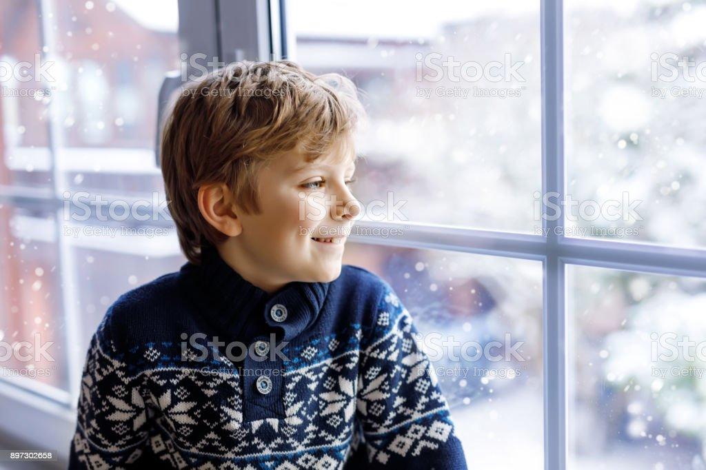 Glückliches Kind entzückende junge sitzt in der Nähe von Fenster und nach draußen im Schnee am Weihnachtstag oder am Morgen. – Foto