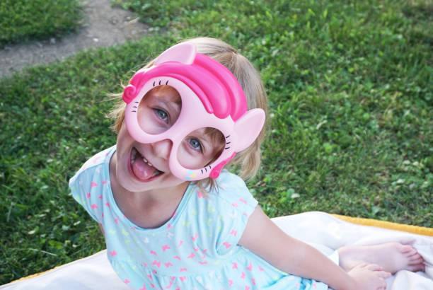 glücklich entzückende kleine mädchen lustiges gesicht mit maske zu - cro maske stock-fotos und bilder