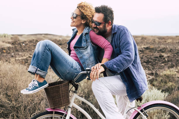 happy adult caucasian, couple having fun with bicycle in outdoor leisure activity. concept of active playful people with bike during vacation - everyday joy lifestyle without age limitation - laughing a lot people middle age stock photo