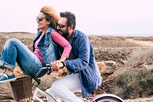 gelukkige volwassen kaukasische, paar plezier met fiets in openlucht recreatieve activiteit. concept van actieve speelse mensen met fiets tijdens vakantie - dagelijkse vreugde levensstijl zonder leeftijd beperking - man voeren vrouw en zowel veel plezier e - ouder volwassenen koppel stockfoto's en -beelden