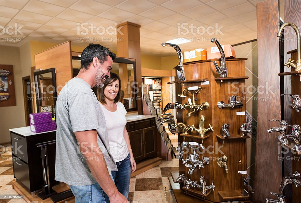 Happy adult couple looking at bath faucet stock photo