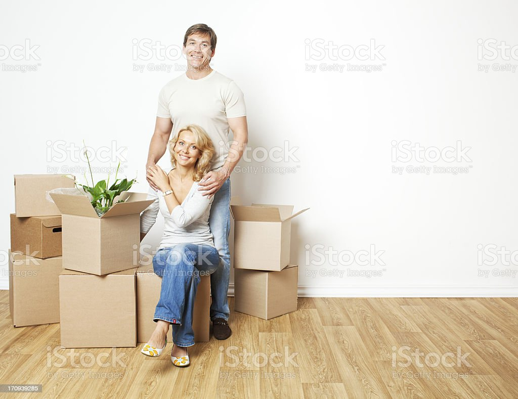 Happy adult couple moving into new home and packing boxes. royalty-free stock photo