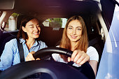 Portrait of happy adult daughter driving her mother in car, smiling and looking camera
