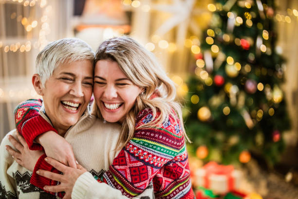 happy adult daughter embracing her senior mother on new year's day. - family christmas imagens e fotografias de stock
