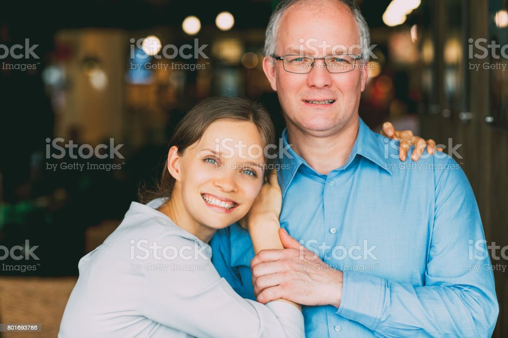 Happy Adult Daughter Embracing Middle-aged Father stock photo