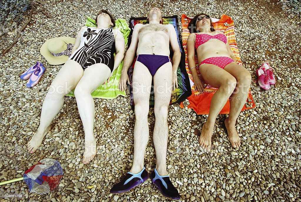 Happy adult friends on the bech. stock photo