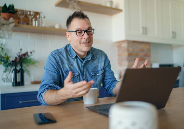 Happy adult man having a video call with a laptop at home Happy adult man having a video call with a laptop zoom stock pictures, royalty-free photos & images