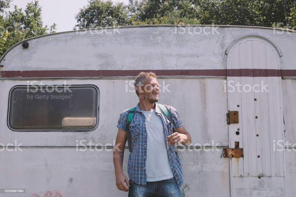 Happy adult man hiker in front of his parked old vintage camper - Royalty-free 40-44 Years Stock Photo