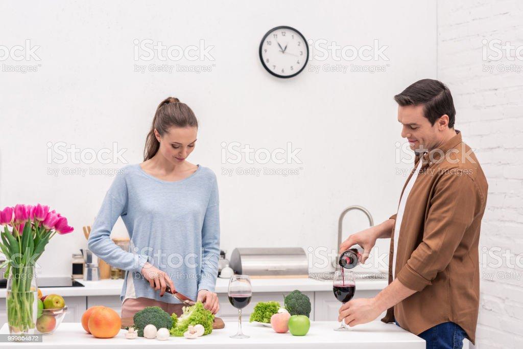 homem adulto feliz derramando vinho em vidro para esposa enquanto ela cozinha - foto de acervo