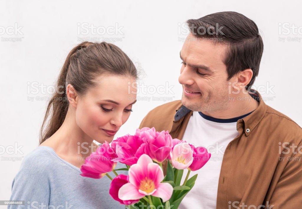 homem adulto feliz apresentando buquê de tulipas para mulher - foto de acervo