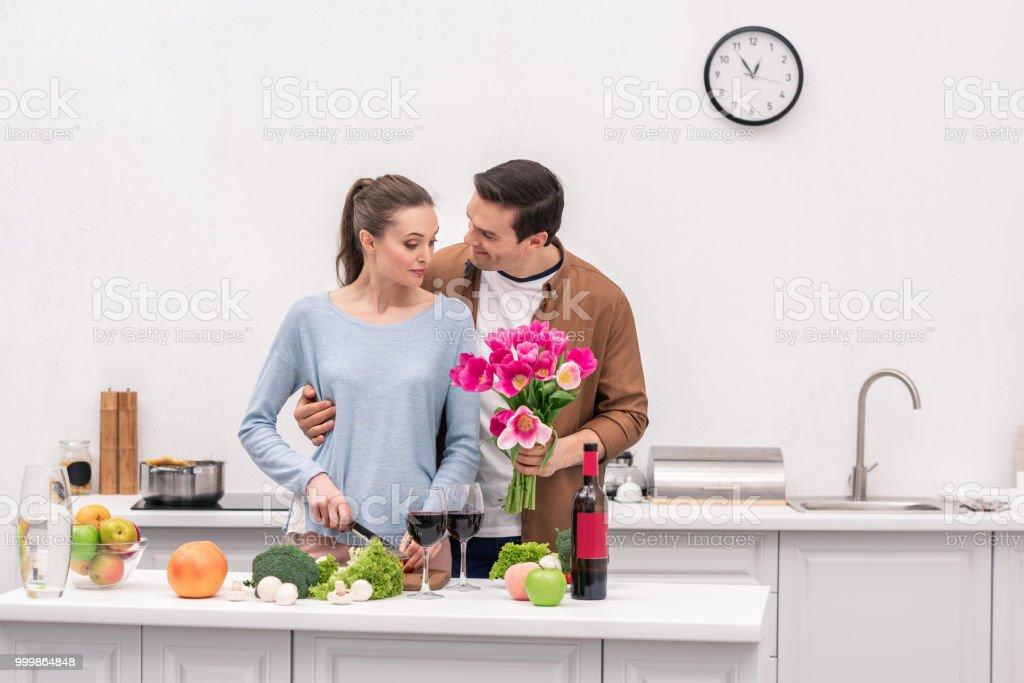 homem adulto feliz apresentando buquê de tulipas para esposa enquanto ela cozinha - foto de acervo