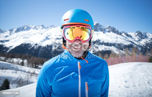 Happy adult man skiing and looking at the camera wearing goggles and a helmet