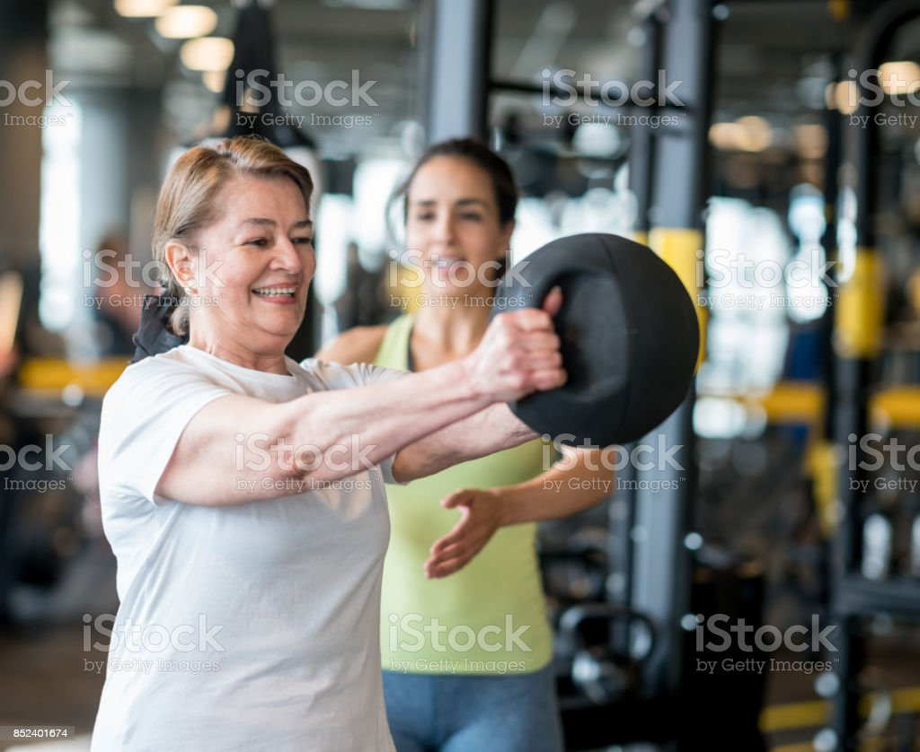 Happy adult woman exercising at the gym with her coach stock photo