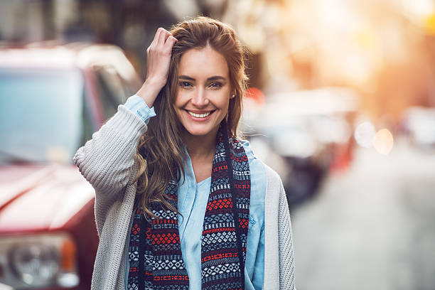 Happy adult woman smiling outdoors and walking on city street stock photo