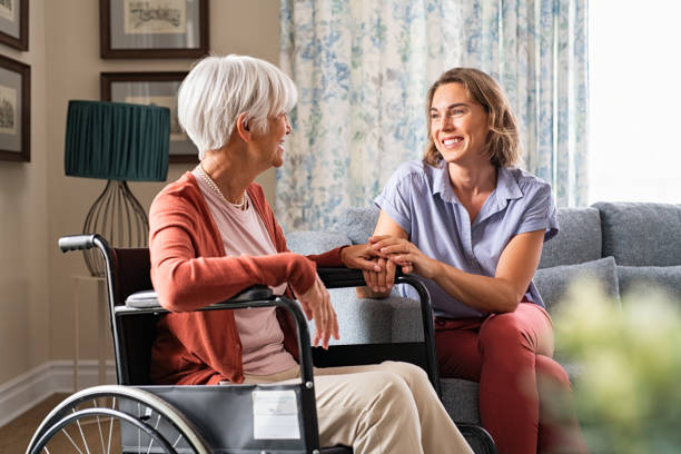 Happy adult woman visiting her elderly mother at home stock photo