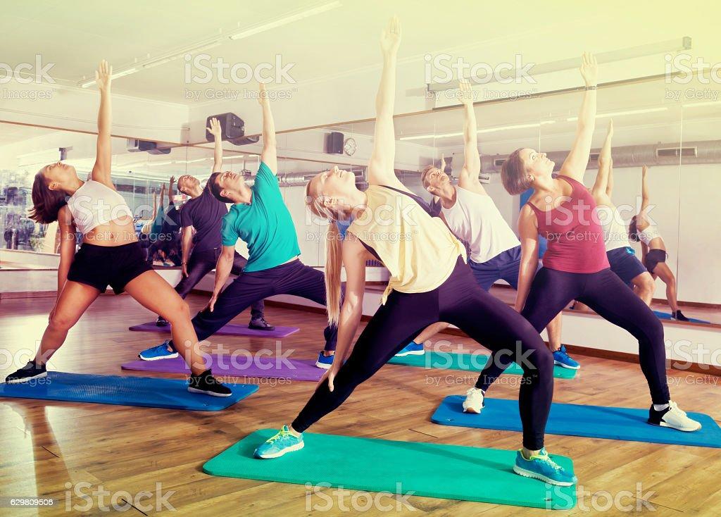 Happy adults having group fitness class - foto de acervo