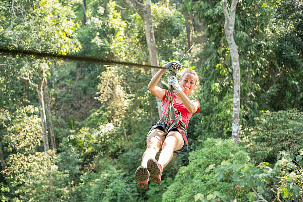 Happy adventurous woman on a zip-line crossing the jungle Young healthy woman enjoying zip-lining  on a canopy tour adventure in the rain forest in northern Laos, sunny summer day. zip line stock pictures, royalty-free photos & images