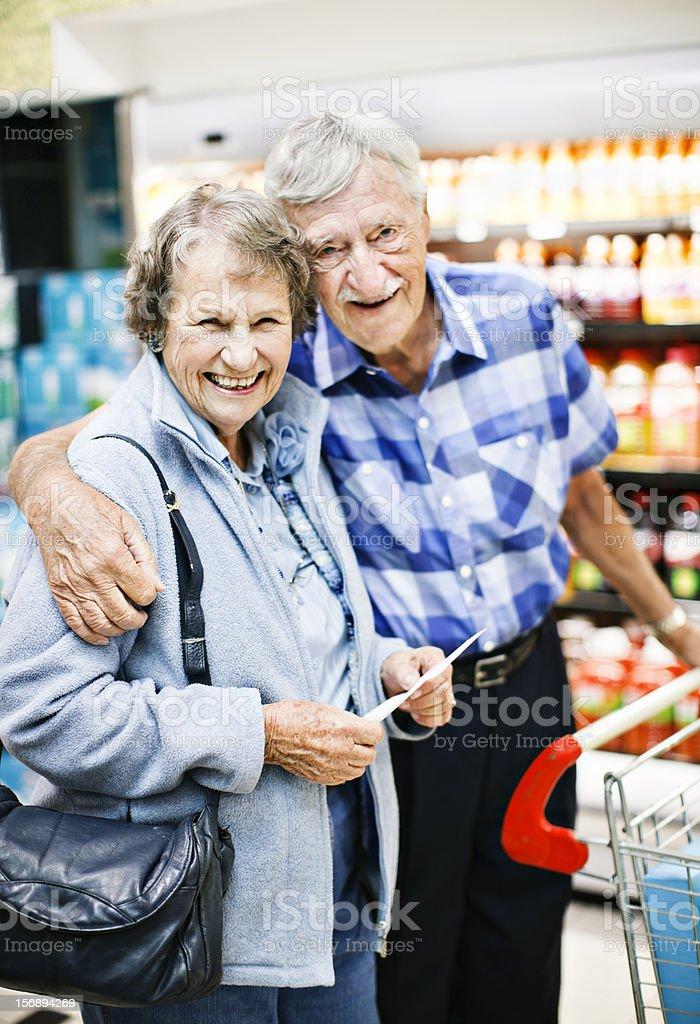 Happy, affectionate senior couple shopping in supermarket stock photo