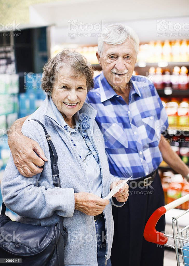 Happy, affectionate senior couple shopping in supermarket royalty-free stock photo
