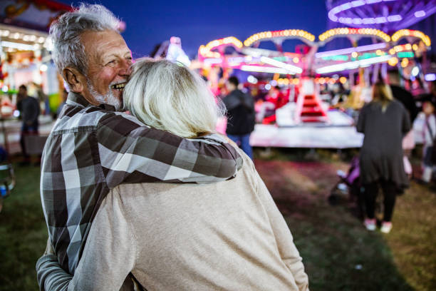 Happy affectionate seniors enjoying at amusement park by night/ Happy senior man embracing his wife while spending their night at amusement park. real life stock pictures, royalty-free photos & images