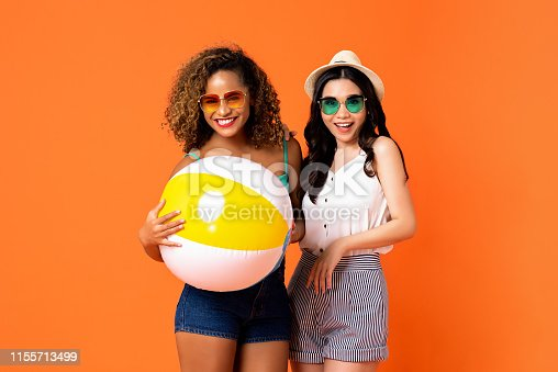 istock Happy African American and Asian woman friends with colorful beach ball 1155713499