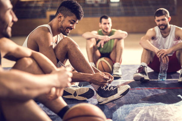 Happy African American basketball player tying shoelace while relaxing on basketball court with friends. stock photo