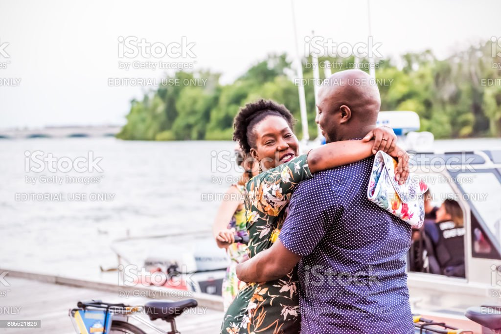 Happy African American black couple smiling hugging and embracing, standing in Georgetown park on riverfront in evening with potomac river and boat stock photo
