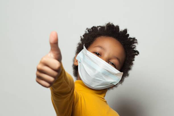 enfant noir afro-américain heureux dans le masque protecteur médical de visage affichant le pouce vers le haut sur le blanc - masque enfant photos et images de collection