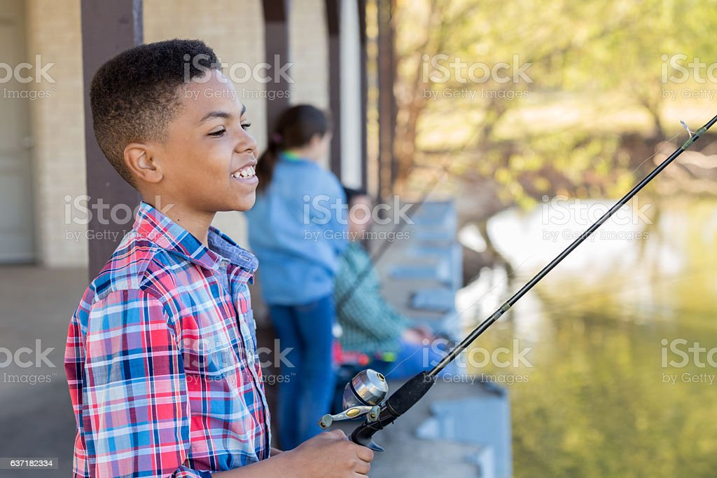 Happy African American boy fishes with friends stock photo
