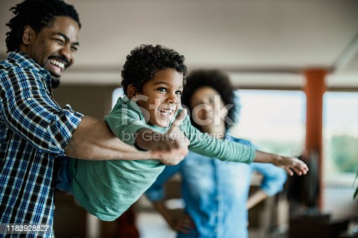 Happy black boy having fun while playing with his father at home. Woman is in the background.