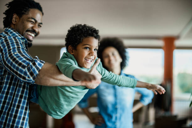 Happy African American boy having fun with his father at home. stock photo
