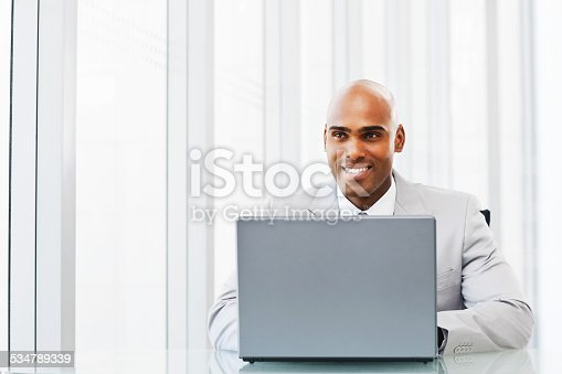 1053499704 istock photo Happy African American business man working on laptop 534789339