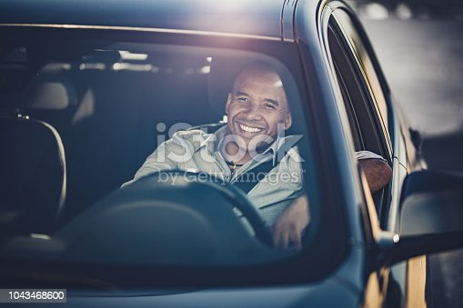 Happy black businessman enjoying while driving a car.