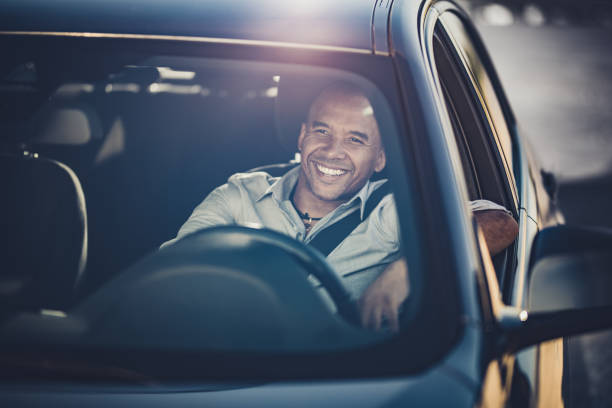 Happy African American businessman going on a trip by car. stock photo