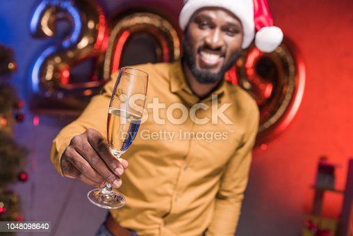istock happy african american businessman in santa hat showing glass of champagne at new year corporate party 1048098640