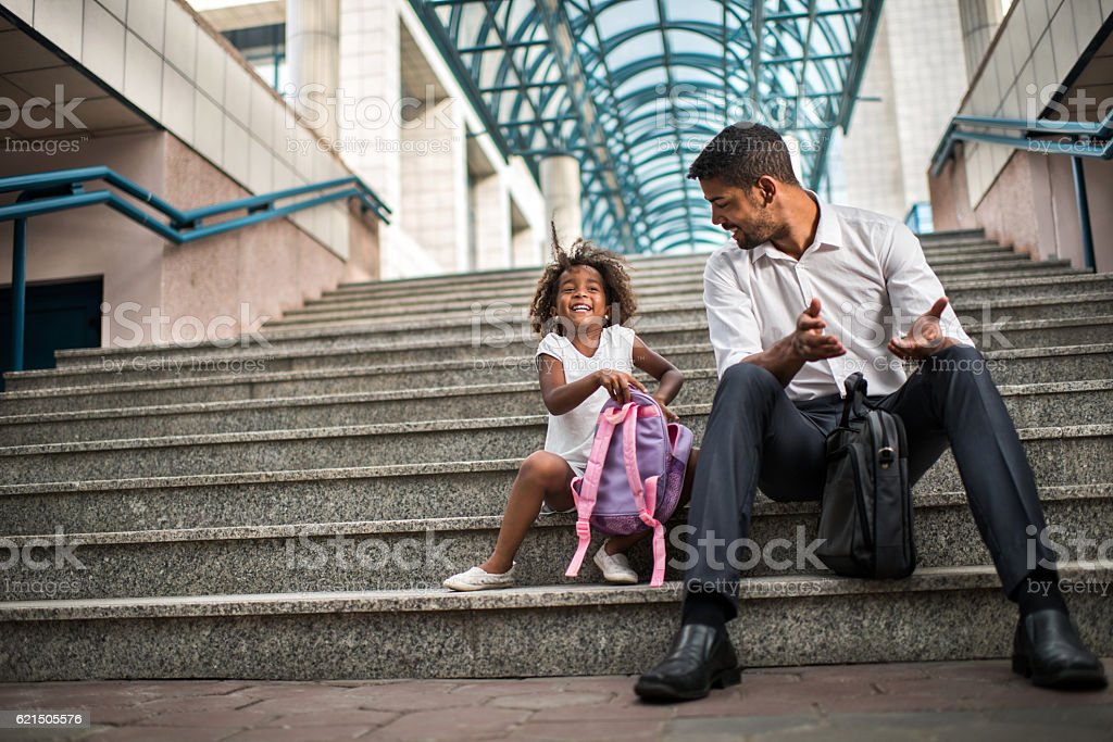 Happy African American businessman relaxing with his daughter on stairs. foto stock royalty-free
