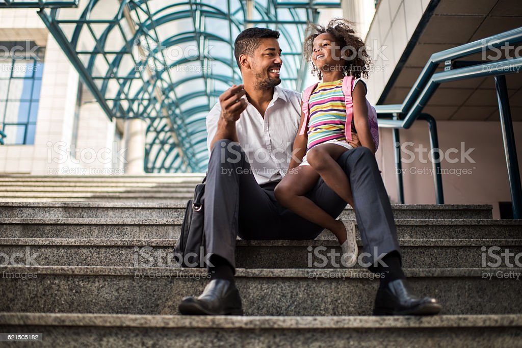 Happy African American businessman talking to his daughter on stairs. photo libre de droits