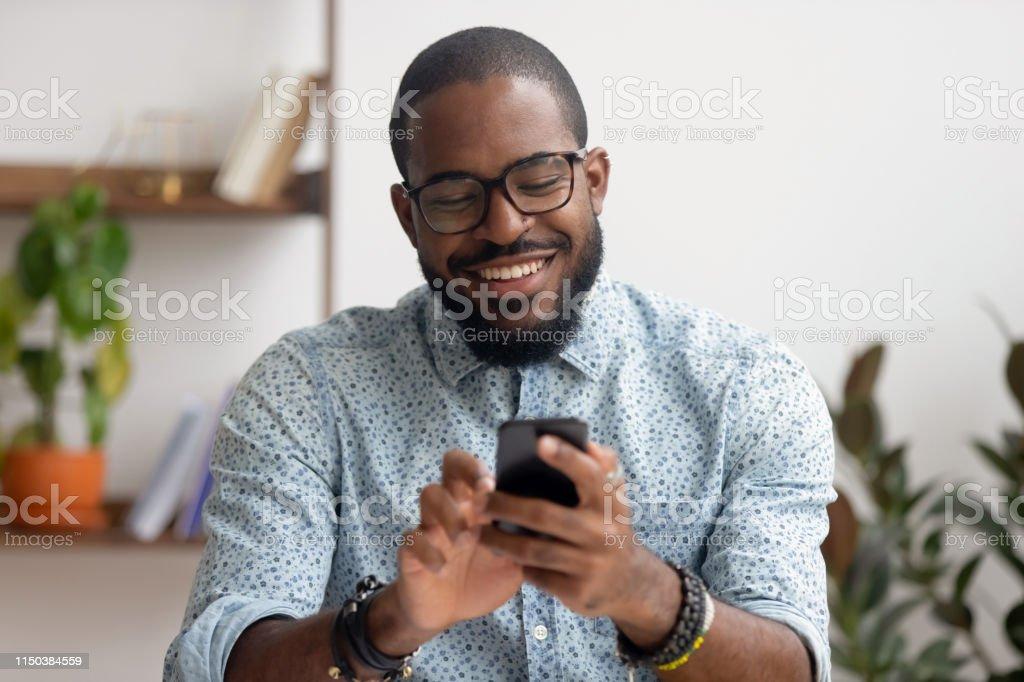 Homem de negócios americano africano feliz que usa apps móveis do telefone no local de trabalho - Foto de stock de Adulto royalty-free