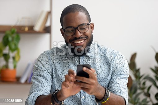istock Happy african american businessman using phone mobile apps at workplace 1150384559
