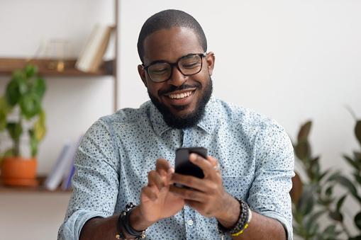 Foto de Homem De Negócios Americano Africano Feliz Que Usa Apps Móveis Do Telefone No Local De Trabalho e mais fotos de stock de Adulto