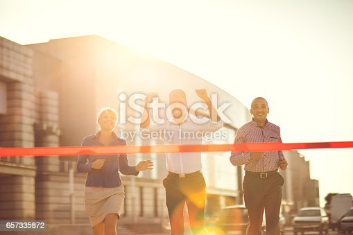 Group of smiling business colleagues running at sunset. African American businessman is winning the race.