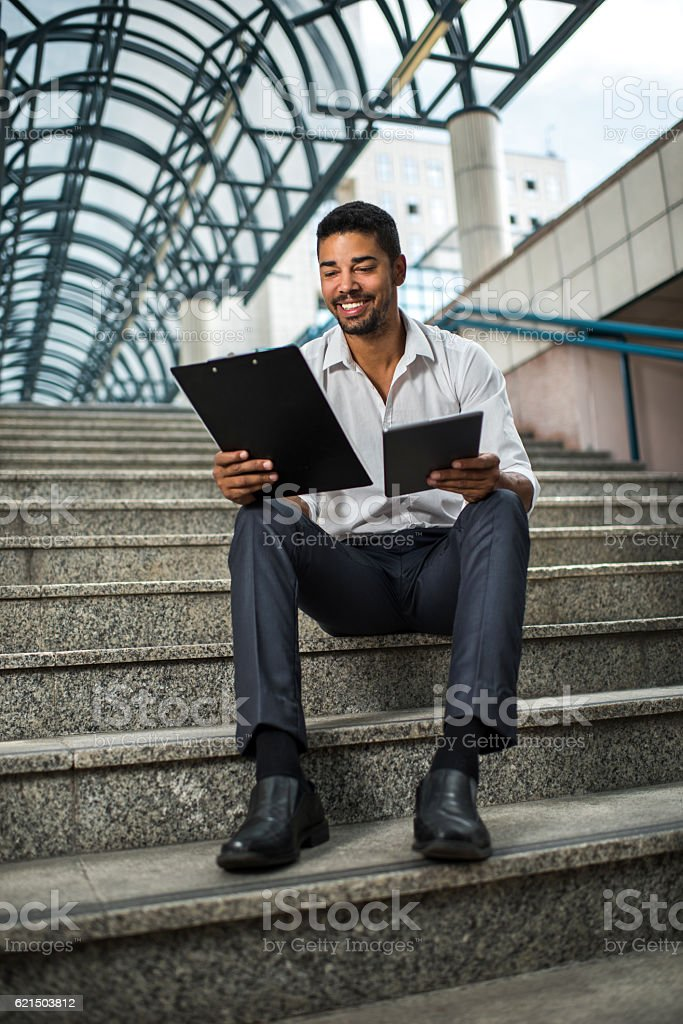 Happy African American businessman working on the stairs. photo libre de droits